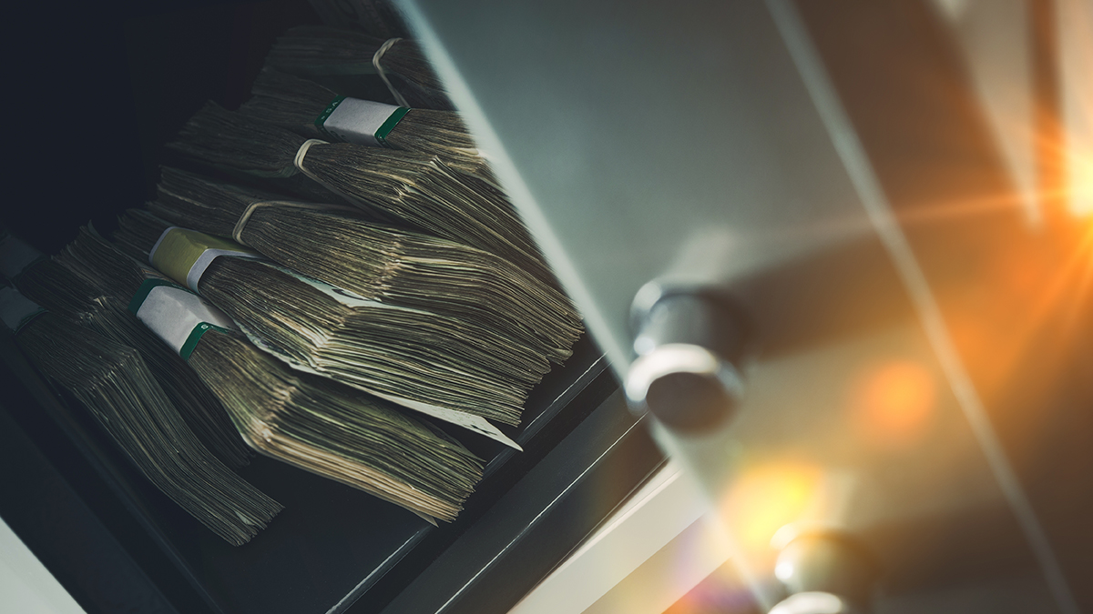 Money in safe (welcomia/Shutterstock.com)